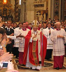 Pope Benedict XVI, wearing robes of red and white, is walking in procession in St. Peter's, and raising his hand in blessing.