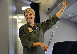 Woman in olive-green fatigues holding passenger oxygen mask in aircraft cabin
