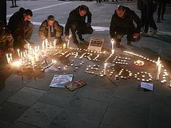 Des personnes s'asseyent le temps d'un instant pour mettre en place des bougies commémoratives traçant un Charlie Hebdo
