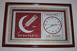 "Welfare Party - A clock displaying the emblem of the Welfare Party. The party slogan translates as ""Justice is our goal."""