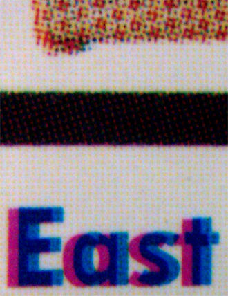 Printing registration - An example of registration misalignment, note the cyan and magenta plates are not in the exact place. Also halftones are visible on the top area.