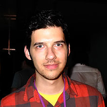 Vreeland's face is close-cropped and bright with a harsh flash. He is in a very dark, indoors setting, and wears a red and black plaid shirt. He is white and has short, dark hair, some stubble, and no glasses.