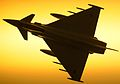 Royal Air Force Typhoon F2 jet fighter is silhouetted against the sky as it passes overhead.jpg
