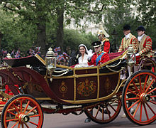 Couple sitting in a decorated horse-drawn open-top carriage, with two footmen in livery sitting behind the newly-weds.