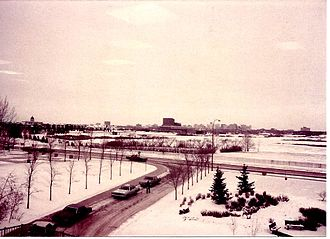 Conexus Arts Centre - Saskatchewan Centre of the Arts winter 1980-81 from University of Regina Laboratory Building before original plans for exterior could be followed; showing Wascana Centre setting, Legislative Building and downtown Regina beyond