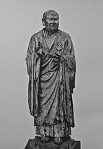 Seshin. Front view of a lifelike statue. Both arms are bend with the palm of the left hand turned upward and the right hand pointing up. Black and white photograph.