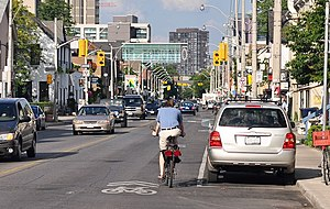 A shared-lane marking in Toronto, Ontario, Canada. Note that the cyclist is not properly positioned on the roadway. Cyclists should ride over the sharrow