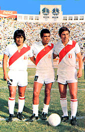Photo of three men, wearing all-white uniforms marked by a red diagonal stripe in their jerseys, inside a stadium filled with spectators