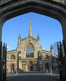 View through an archway of end of a church with a central door flanked by canopied niches containing statues. Arched window above the door and spire behind.