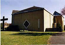 A modern Church of England church. A large concrete crucifix, of similar height to the church, is beside the building.