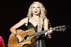 Una adolescente de cabello rubio y ojos azules, vestida con un vestido brillante, mira hacia adelante y toca una guitarra de madera de koa.