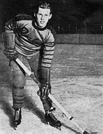 Syd Howe posing on the ice in a Philadelphia Quakers uniform