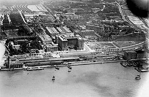 Tsim Sha Tsui - Aerial view of Tsim Sha Tsui in early 20th century. The Kowloon Station (low left corner), the former Marine Police Headquarters (on the hill inland behind the station), and the Peninsula Hotel (centre)