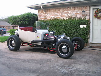 "Hot rod - A 1923 Ford T-bucket in the traditional style with lake headers, dog dish hubcaps, dropped ""I"" beam axle, narrow rubber, and single 4-barrel, but non-traditional disc brakes"