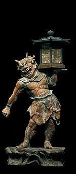 Tentōki. Front view of a stocky statue with a demon face. He is carrying a lantern on is left shoulder supported by his left hand. Black and white photograph.
