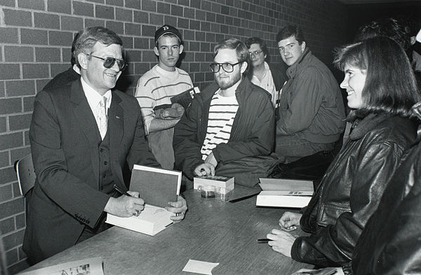 The popular demand for Tom Clancy's action novels exceeded his ability to write new books. As a result, his publisher hired ghostwriters to write novels in the Clancy style. Tom Clancy at Burns Library, Boston College.jpg