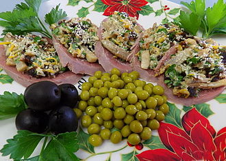 Beef tongue - Russian zakuski: cold cuts of tongue topped with mushrooms, cheese, nuts and prunes