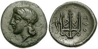 "Troezen - Coin (chalkous) from Troezen, 325–300 BC. Obverse: Head of Athena wearing tainia. Reverse: Ornate trident head; to left, dolphin upward, ΤΡΟ(ΙΖΗΝΙΩΝ) ""of Troizenians"""