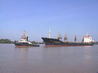 Gironde estuary - Tug helping a bulk carrier on Gironde estuary to approach a subsidiary of Bordeaux port.