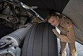 U.S. Air Force Capt. Philip Bush, a pilot with the 816th Expeditionary Airlift Squadron, inspects the landing gear on a C-17 Globemaster III aircraft at Al Udeid Air Base, Qatar, before taking off on a mission 140109-F-AM664-001.jpg