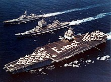 Three ships sale next to each other, including an aircraft carrier which has jets arranged as an arrow and the phrase E=MC2 written with sailors on deck