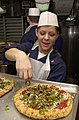 US Navy 030419-N-1577S-001 Information Systems Technician 1st Class Shannea Vorous prepares pizza for the crew of USS Nimitz (CVN 68) and Carrier Air Wing 11 (CVW-11) as part of the First Class Pizza Night.jpg