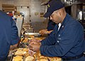 US Navy 050905-N-4008C-008 U.S. Navy Chief Selectee Aviation Boatswain's Mate Brian Wilson, assigned to the amphibious assault ship USS Bataan (LHD 5), prepares breakfast for survivors of Hurricane Katrina.jpg