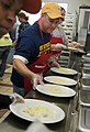 US Navy 090414-N-1722M-201 Personnel Specialist 3rd Class Don Martelli, assigned to the Arleigh Burke-class guided-missile destroyer USS Stockdale (DDG-106), serves meals at the Oxnard Rescue Mission.jpg