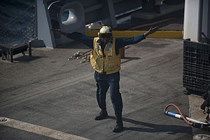 US Navy 120104-N-PB383-864 A civilian landing signalman lands a helicopter during a replenishment at sea.jpg