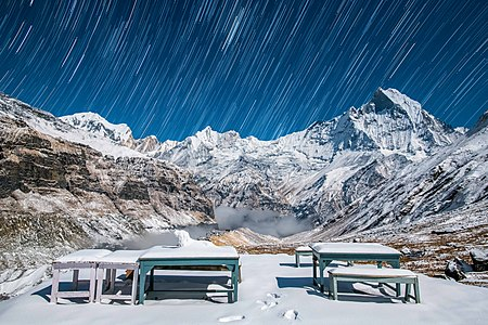 The view of Machhapuchre from Annapurna base camp with fresh snow under moonlight and the trails of stars over it.