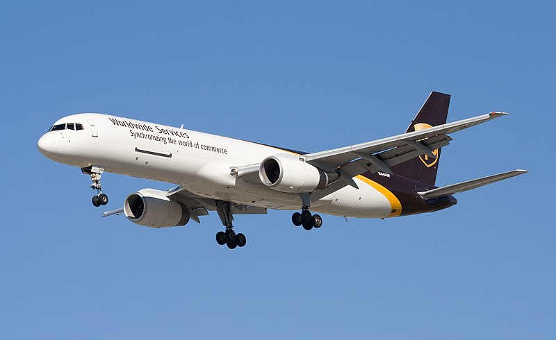 Side quarter view of UPS twin-engine jet in flight, with gear extended.