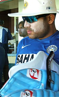 A man in the blue Indian cricket practice kit, wearing sun cream, sunglasses and a hat carrying his batting pads. Others can be seen in the background.