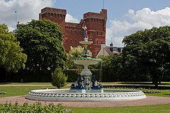Ornate circular fountain surrounded by grassy area with trees and red brick building in the background.