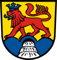 Or, a lion statant gules, crowned and langued azure, on a triple-peaked mountain azure, with a rock(?) argent in base