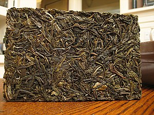 A compressed brick of pu-erh tea . Individual leaves can be seen on the surface of the brick.