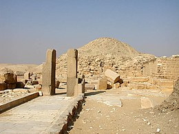 Photograph of a path, two vertical columns and main pyramid.