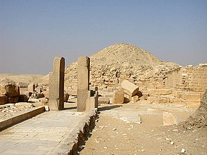 A photo taken near the end of the causeway. Left of centre stand two pillars that remain of the granite doorway constructed by Teti. The damaged walls of the mortuary temple are visible in the background, with the pyramid standing over them further into the background.