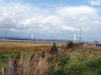 Overhead line crossing - The two masts of the high level crossing of the River Severn estuary between England and Wales, with the Severn Bridge behind.  These masts are 1.6km (1 mile) apart: a further 1.2-km line crosses the River Wye estuary to the left.