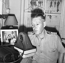 Indoor half portrait of man in light-coloured military uniform speaking into radio transmitter with a family photo to his right