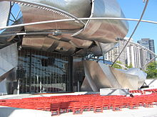 A large bandshell stage, closed off by a glass door, is framed by large curved plates of shiny metal. A large number of red seats are in front of the stage, with a metal trellis forming triangular and diamond shapes above. Large buildings are in the background at right.