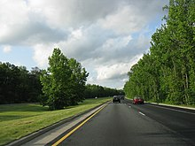A four-lane limited access parkway lined with trees on the sides and in the median.