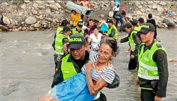 Venezuelan migrants crossing a river, aided by Colombian police