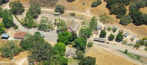 An aerial shot of a large ranch. Trees surround several huts and buildings on the barren property.