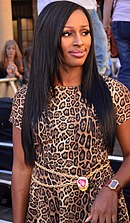 A woman with long black hair wearing an animal print dress