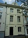 foto van Huis uit het 3e kwart van de 19e eeuw met gepleisterde gevel, voorzien van vensteromlijstingen en een topgevelachtige afsluiting