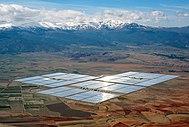Store reflekterende rektangler som består av solcellepaneler midt på en slette.