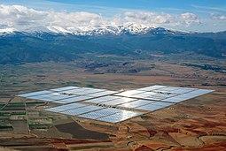 Arka planda karlı dağlar ile düz bir ovada parlayan dikdörtgenler halinde düzenlenmiş mesafede konsantre güneş enerjisi parabolik olukları