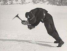 a man in polar gear leans into the face of high winds while attempting to swing an ice axe