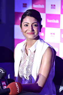 Anushka Sharma, dressed in a sleeveless white jacket and a floral top, is smiling at the camera.