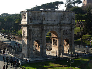 Meta Sudans - The Arch of Constantine seen from the Colosseum. The foundation of the Meta Sudans is visible in the brown circular region just in front of the arch
